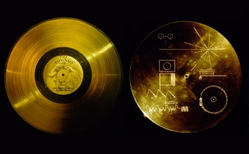 """Flying aboard Voyagers 1 and 2 are identical """"golden"""" records, carrying the story of Earth far into deep space. The 12 inch gold-plated copper discs contain greetings in 60 languages, samples of music from different cultures and eras, and natural and man-made sounds from Earth. They also contain electronic information that an advanced technological civilization could convert into diagrams and photographs. The cover of each gold plated aluminum jacket, designed to protect the record from micrometeorite bombardment, also serves a double purpose in providing the finder a key to playing the record. The explanatory diagram appears on both the inner and outer surfaces of the cover, as the outer diagram will be eroded in time. Currently, both Voyager probes are sailing adrift in the black sea of interplanetary space, having left our solar system years ago. This gold aluminum cover was designed to protect the Voyager 1 and 2 """"Sounds of Earth"""" gold-plated records from micrometeorite bombardment, but also serves a double purpose in providing the finder a key to playing the record. The explanatory diagram appears on both the inner and outer surfaces of the cover, as the outer diagram will be eroded in time. Flying aboard Voyagers 1 and 2 are identical records, carrying the story of Earth far into deep space. The 12-inch gold-plated copper discs contain greetings in 60 languages, samples of music from different cultures and eras and natural and man-made sounds from Earth. They also contain electronic information that an advanced technological civilization could convert into diagrams and images. Image credit: NASA"""